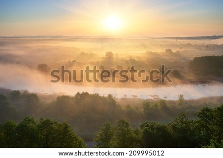 Summer landscape with fog over the river. The first rays of the rising sun paint mist - stock photo