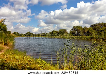 Summer landscape with lake and blue sky - stock photo