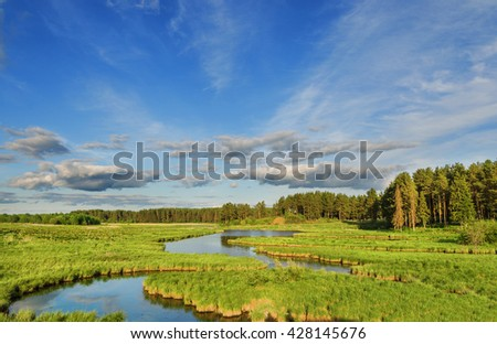 summer landscape with river and clouds on blue sky in the rays of the setting summer sun