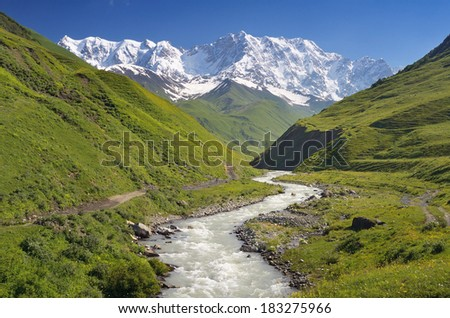 Summer landscape with river and mountain snow. Peak Shkhara Zemo Svaneti, Georgia. The main Caucasian ridge - stock photo