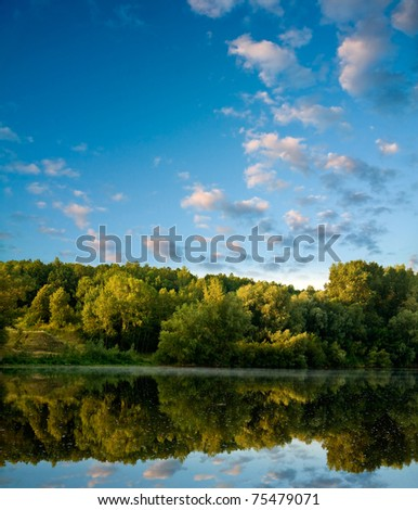 Summer landscape with river and pink clouds on blue sky. - stock photo