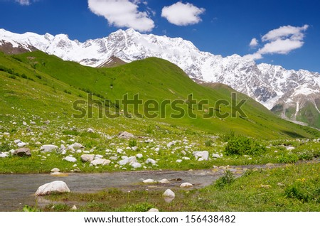 Summer landscape with river under snow-covered mountain. Shkhara Mountain, Georgia, the Main Caucasian Ridge