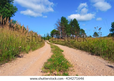 Summer landscape with road, sky, clouds, grass and trees  - stock photo