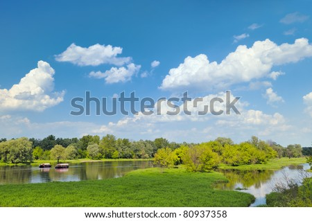 Summer landscape with two gondolas flowing by the river - stock photo