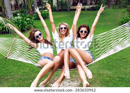 Summer lifestyle portrait of tree girls going crazy, screaming, laughing having fun together, jumping at hammock.  wearing white tops and sunglasses, ready for party,  joy, fun. - stock photo