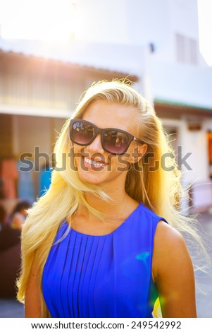 Summer lifestyle portrait of young sexy smiling woman in a blue dress and a fashion sunglasses. - stock photo