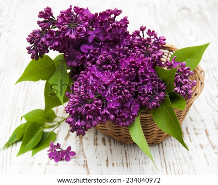 summer lilac flowers in basket on a wooden background - stock photo