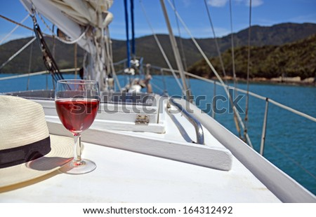 Summer Luxury - a glass of Rose and a Panama hat on the deck of a yacht in the Marlborough Sounds, New Zealand. - stock photo