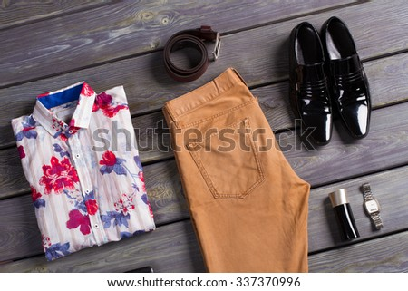 Summer men's clothing on a dark wooden background. - stock photo