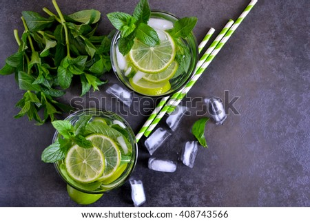 summer mojito cocktail with mint and lime on black background, top view  - stock photo