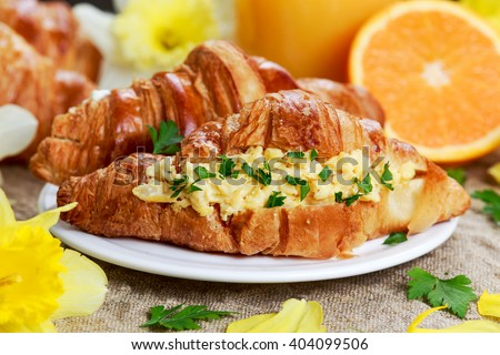 Summer Morning Breakfast Croissant stuffed scrambled eggs decorated with flowers. - stock photo