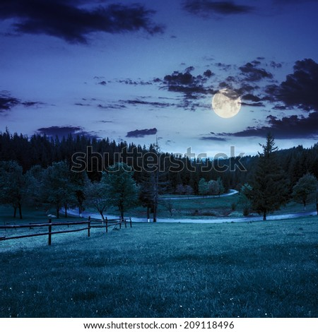 summer mountain landscape. curve asphalt road and wooden fence near the meadow on hillside with forest at night in full moon light - stock photo