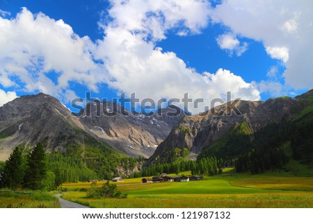 Summer mountain landscape with chalet on a meadow and road in the foreground, Sertig Dorfli, Davos, Switzerland