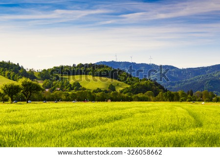 Summer mountain valley with crops growing on fields, a road and windmills in the distance. Germany, Black Forest. Scenic agricultural landscape. - stock photo