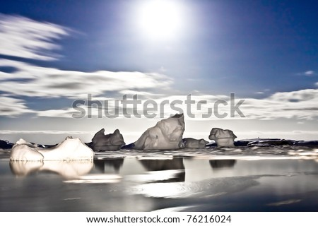 Summer night in Antarctica.Icebergs floating in the moonlight - stock photo