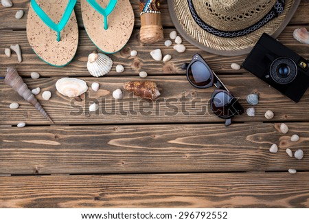 Summer objects among sea shells and stones on wooden background. Flip-flops, straw hat, sunglasses, photocamera are the must to take. - stock photo