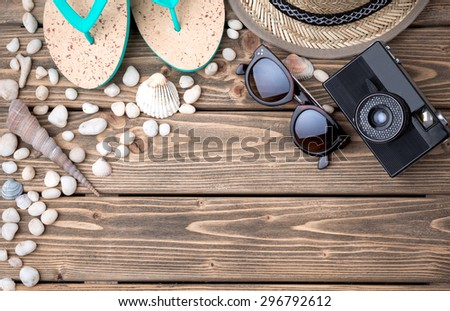 Summer objects for vacation laid on wooden floor among sea shells and stones. Flip-flops, straw hat, sunglasses and photocamera are the must. - stock photo