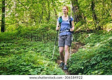 Summer outdoor activity - a woman hikes down a narrow footpath in a green forest. - stock photo