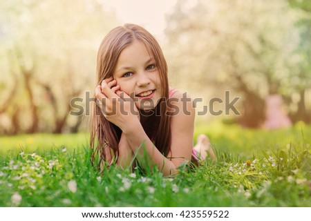 summer outdoor close up portrait of beautiful happy kid girl lying on the grass in park