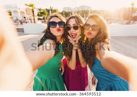 Summer outdoor portrait of three friends fun girls  taking photos with a smartphone at bright sunset. Group of happy women  taking self-portrait on their travel vacations. Wearing colorful dress. - stock photo