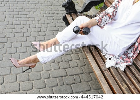 Summer outfit, street fashion look. Young tanned beautiful woman in white pants and light floral pink patent in leather high-heeled shoes. Stylish girl sitting on a bench in the city.  - stock photo