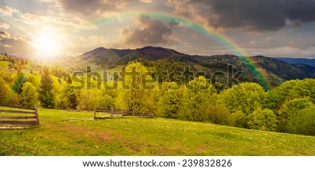 summer panorama landscape. fence near the meadow path on the hillside. forest in fog on the mountain in sunset light with rainbow - stock photo