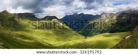 Summer panorama of Austrian Alps with green hills, grass and clouds. View from Grossglockner High Alpine Road. - stock photo