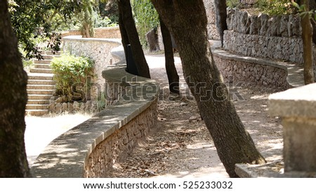 Summer park paths with stone fences and trees on a dry sunny day