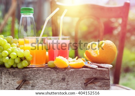 Summer Party Outdoor Fresh Fruits Juice Beverages Wooden Board Chair Sun Rays - stock photo