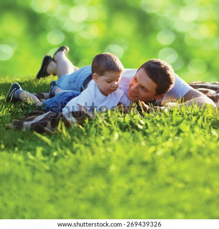 Summer photo happy father and son together lying on fresh green grass, life moment family resting on the nature - stock photo