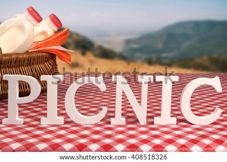 Summer Picnic Scene In The Mountain.  White Wooden  Sign Picnic, Wicker Basket Close Up With Bottles Of Milk  On The Red Checkered Tablecloth