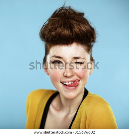 Summer portrait, beautiful freckled young woman with tongue, wearing yellow cardigan. Blue background. Studio shot      - stock photo