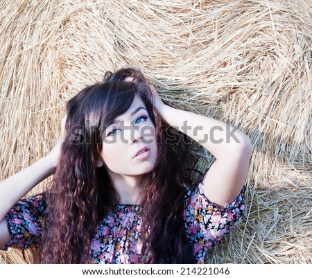 summer portrait of a beautiful longhair country girl on a background of straw.