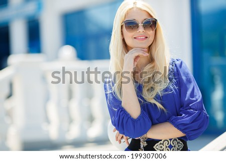 Summer portrait of a beautiful young blonde Caucasian girl with straight hair in blue dress outdoors in the city - stock photo