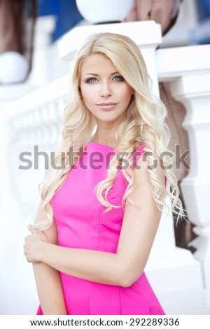 Summer portrait of a beautiful young blonde woman with curly hair in pink dress outdoors in the city. Soft focus - stock photo