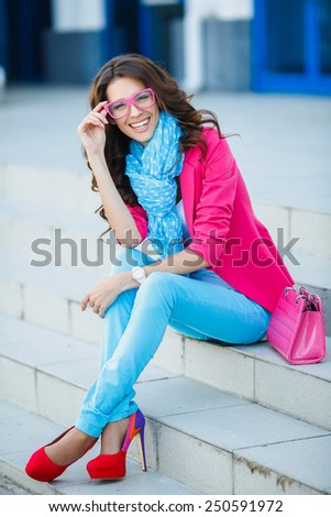 Summer portrait of a beautiful young Caucasian girl with curly hair. Beautiful brunette young woman wearing bright clothes and sitting on the stairs in the street - stock photo