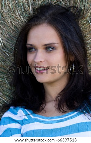 Summer portrait of a girl leaning against a bundle of straw