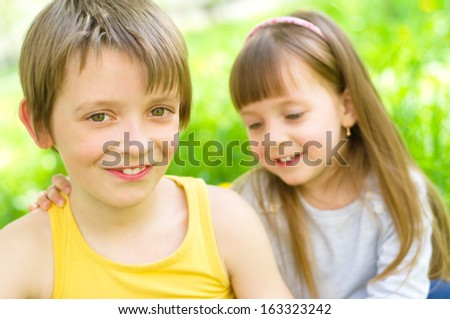 Summer portrait of a happy little girl hugging her brother outdoors - stock photo