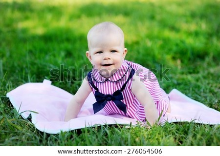 Summer portrait of beautiful baby girl on the lawn