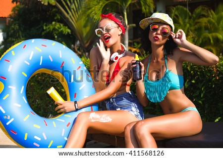 Summer portrait of beautiful stunning blonde and brunette happy girls sitting near the pool on the beach,and green palms background smiling and having fun together with sun cream,funny sunglasses,cool - stock photo