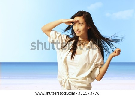 Summer portrait of beautiful young Asian woman on the beach smiling happy, shielding eyes by hand from sunshine. - stock photo