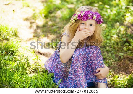 Summer portrait of cute blond girl dressed wreath of lilac on a head in green field. - stock photo