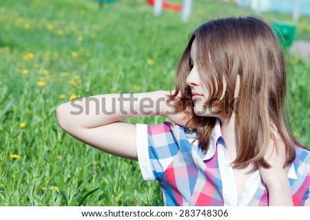 Summer portrait of happy smiling teen girl outdoors.side view
