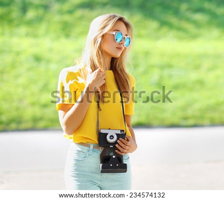 Summer portrait stylish pretty hipster girl in sunglasses with retro vintage camera posing in city, street fashion - stock photo