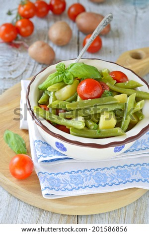Summer potatoes salad with fresh green beans, cherry tomatoes, basil in a rustic cup on a wooden table. Selective focus.