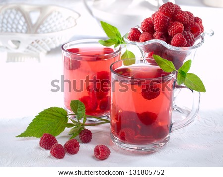 Summer raspberry cold drink (juice, cocktail, fruit tea) with mint on top. - stock photo