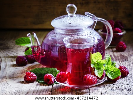 Summer raspberry tea with mint in a glass, vintage wooden background ...