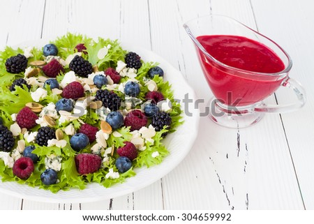 Summer refreshing mixed berry salad with pumpkin seeds, blue cheese, feta and sweet red raspberry vinaigrette - stock photo
