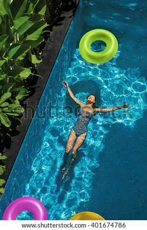 Summer Relax. Beautiful Carefree Happy Young Woman With Sexy Body In Swimsuit Having Fun With Colorful Float Swim Rings Floating In  Swimming Pool Water. Summertime Travel Holidays Vacation. Freshness - stock photo