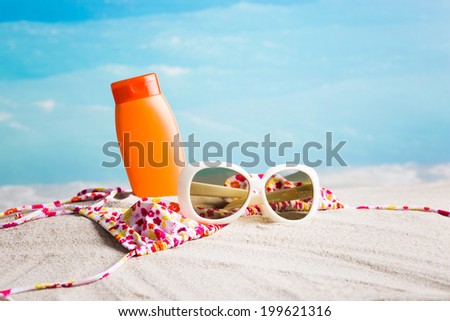 Summer relaxation - swimsuit, lotion and sunglasses on yellow sand - stock photo